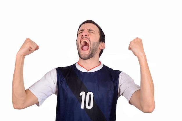 Молодой человек в форме футбола футбола кричащей пока его команда выигрывает. Premium Фотографии