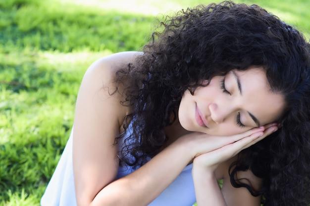 Молодая латинская женщина спит в парке Premium Фотографии