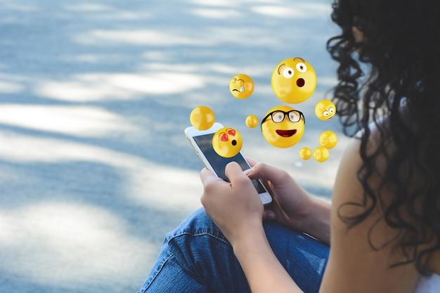 絵文字を送信するスマートフォンを使用して女性 Premium写真