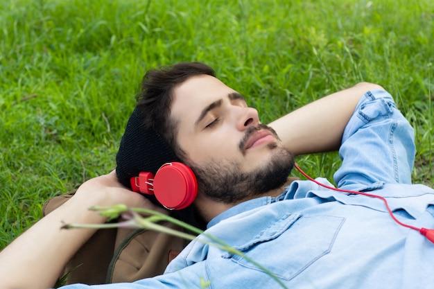 Молодой человек расслабляющий и слушать музыку на траве. Premium Фотографии