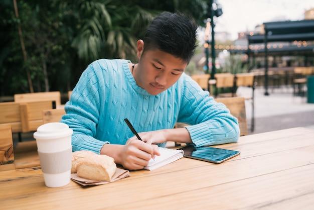コーヒーショップで勉強しているアジア人。 Premium写真