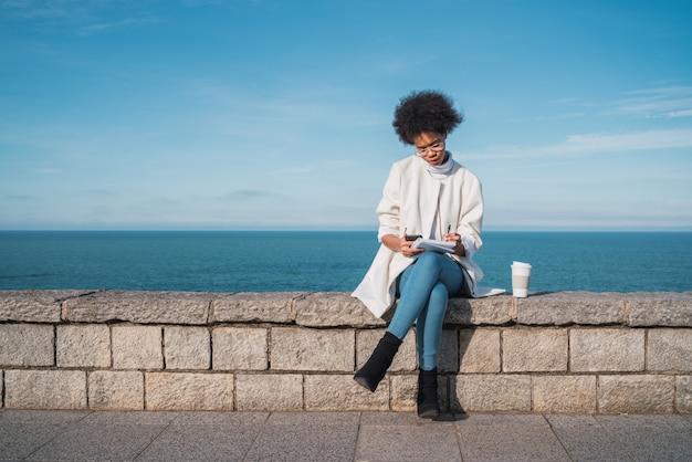 ラテン系女性が屋外で何かを書きます。 Premium写真