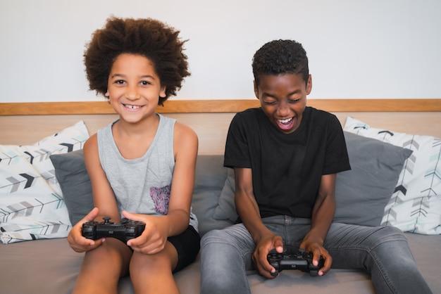 Два брата играют в видеоигры дома. Premium Фотографии