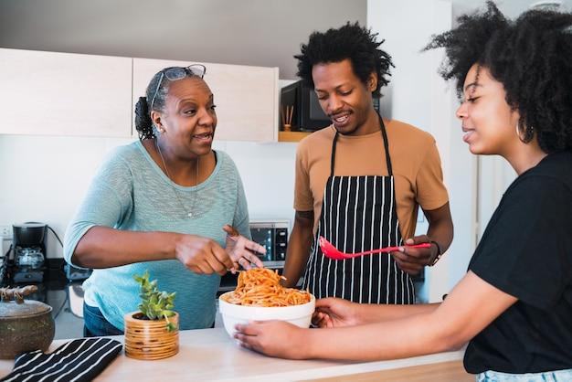 Портрет семьи готовить вместе дома. Premium Фотографии