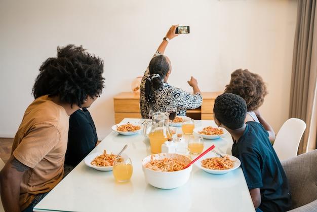 Семья обедает вместе дома. Premium Фотографии