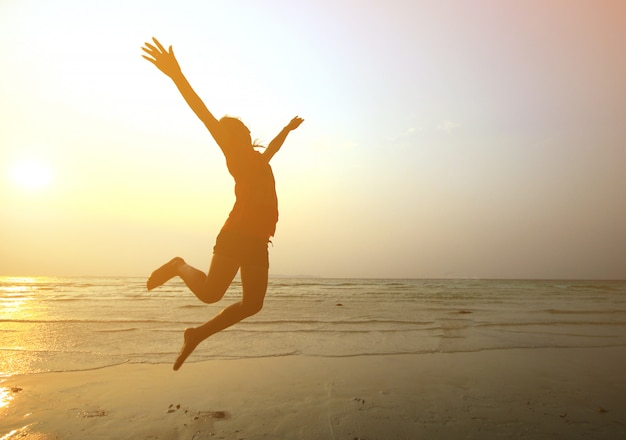 夕暮れ時、ビーチの上を手でジャンプシルエット若い女の子、モーションブラー Premium写真
