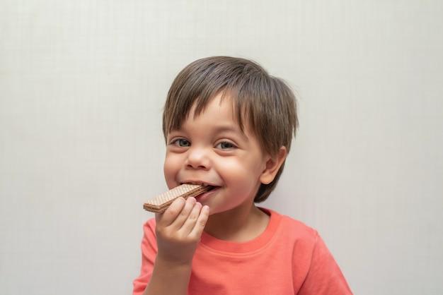 かわいい赤ちゃん男の子幼児 - ウェーハビスケットを食べる Premium写真