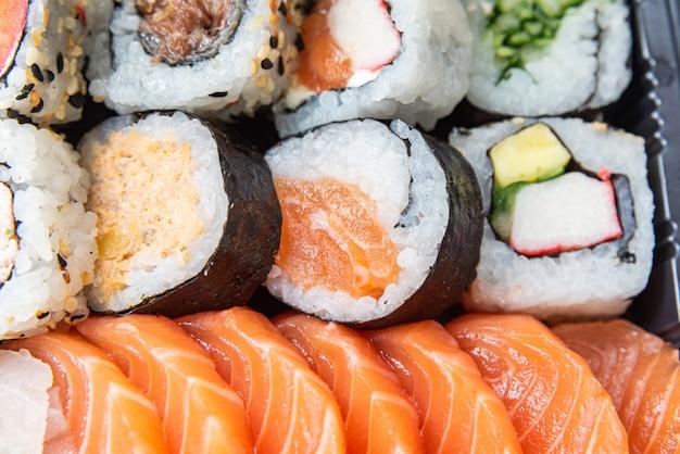 黒いテーブルの上の皿に寿司 無料写真