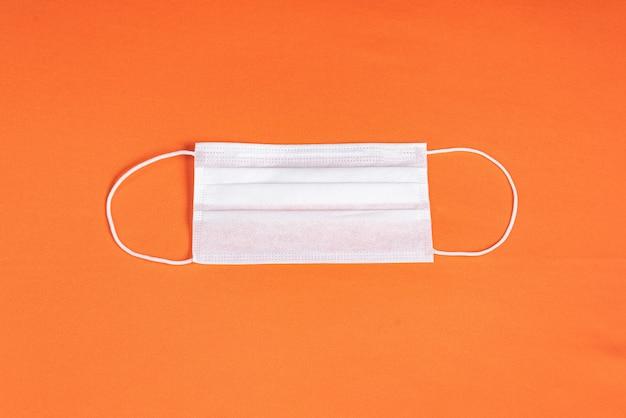 Хирургическая маска на минималистском оранжевом фоне Бесплатные Фотографии