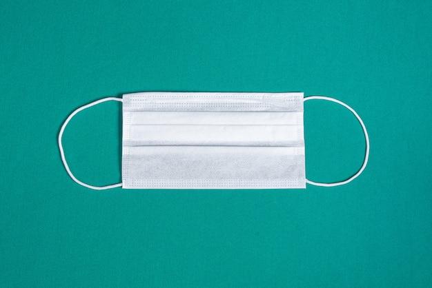ミニマリストの緑の背景の上の外科用マスク 無料写真