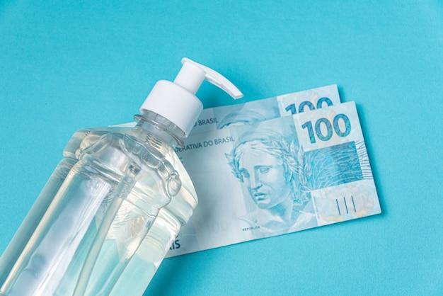 ジェルアルコールとブラジルのリアルマネーが入った容器、 無料写真