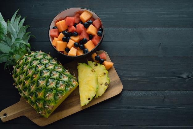 黒い木製の背景にパイナップルとフルーツボウルをスライスしました。上面図。 Premium写真