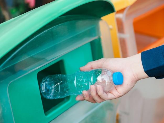 Крупный план руки человека бросая пустую пластичную бутылку с водой в рециркулируя ящик. Premium Фотографии