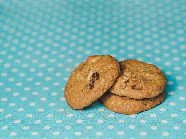 パステルブルーの水玉の背景にオートミールとレーズンのクッキー。 Premium写真
