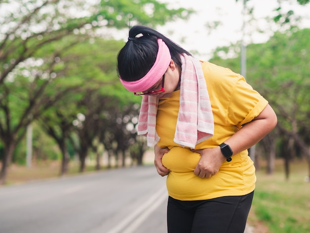 彼女の腹を保持している太りすぎの女性。減量のコンセプト Premium写真