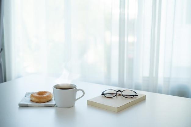 テーブルの上のホットコーヒーとドーナツ Premium写真