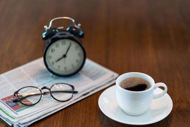 朝の新聞とホットコーヒーカップ Premium写真