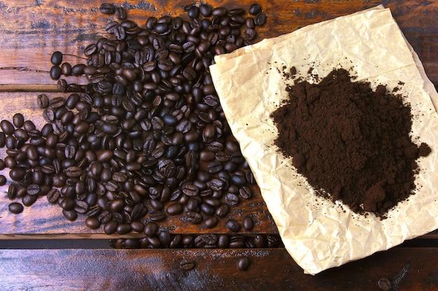 コーヒー豆の焙煎と素朴なテーブルの上の紙の上の挽いたコーヒー。上面図 Premium写真