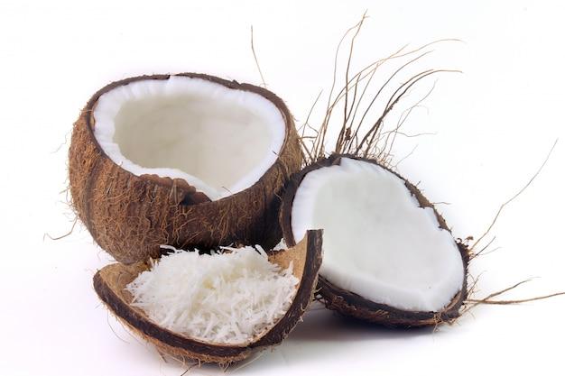 Свежие хлопья кокоса помещенные в изолированной коре и раковине на белой предпосылке. передний план Premium Фотографии