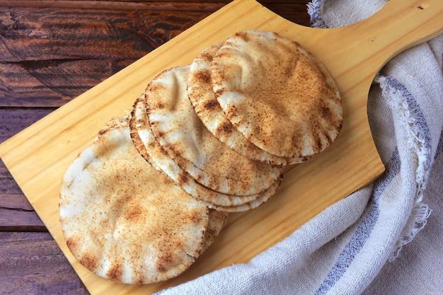 オーブンから出てくる木製のへらで分離されたピタパン Premium写真
