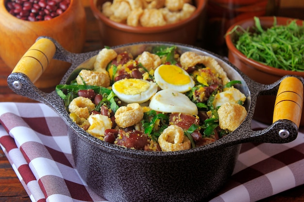素朴な木製のテーブルの上に豆、ベーコン、ソーセージ、コラード、卵で作られたブラジル料理のフェイジャトロペイロの典型的な料理。 Premium写真