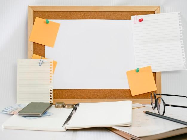 Фон деревянной доски, бумаги для записей, чистого листа бумаги с оборудованием вокруг, таким как карандаши, стаканы, деньги, мобильные телефоны и календари, Premium Фотографии