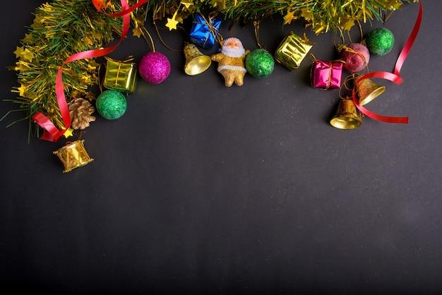 暗い黒背景のクリスマスの装飾。トップビュー、コピースペース。ボール、ギフトボックス、サンタクロース、リボン、松の枝、鐘。 Premium写真