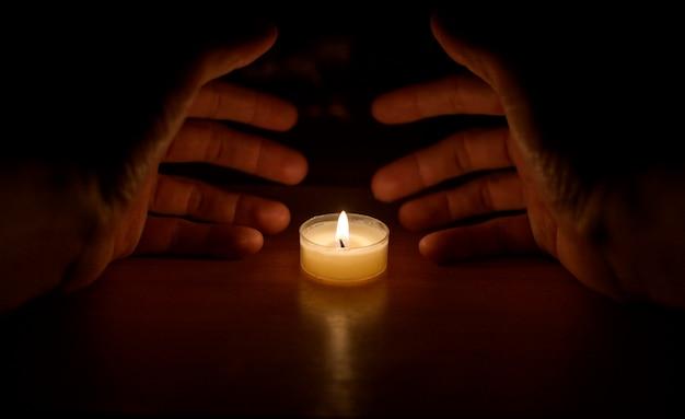 Руки накрыли свечу Premium Фотографии