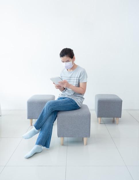 Красивые азиатские женщины работают дома используя таблетку, удобно сидя на диване, во время карантина в пандемии коронавируса. работа на дому и социальной дистанции концепции. Premium Фотографии