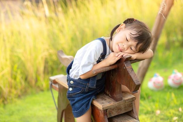 Азиатская девочка маленькая девочка, верхом на деревянной лошади игрушка в саду зеленой травы. Premium Фотографии