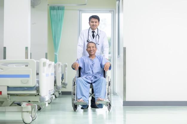 アジアの男性医師と病院の廊下に座っている車椅子のアジア人患者。 Premium写真