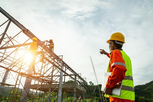 Инженер-техник наблюдает за командой рабочих на высокой стальной платформе, техник-инженер ищет и анализирует незавершенный строительный проект. Premium Фотографии
