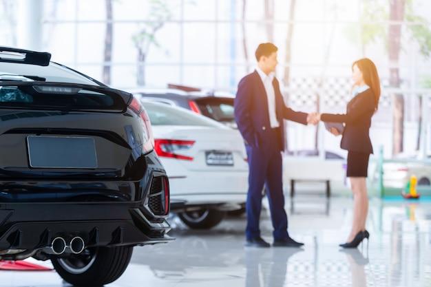 新しい車にセレクティブフォーカスし、ディーラーのプロのセールスマンと彼のクライアントが握手することをぼかします。コンセプトプロフェッショナリズム契約契約リースレンタル小売自動車販売。 Premium写真