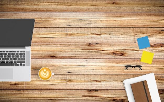 コーヒーカップ、紙、ノート、タブレットまたはスマートフォンと木の上のラップトップでモダンなワークスペース Premium写真