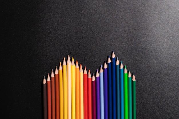 リーダーシップのビジネスコンセプトです。黒の背景に色鉛筆 Premium写真