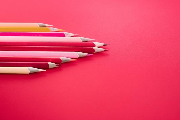 リーダーシップのビジネスコンセプトです。赤い色鉛筆ピンクの背景に他の色を導く Premium写真