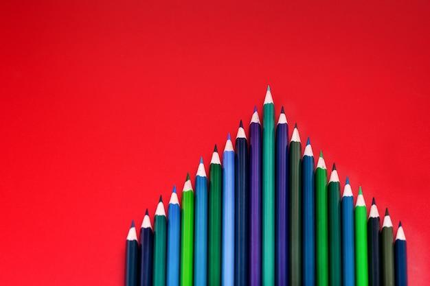 チームワークの概念赤の背景に色鉛筆のグループ Premium写真