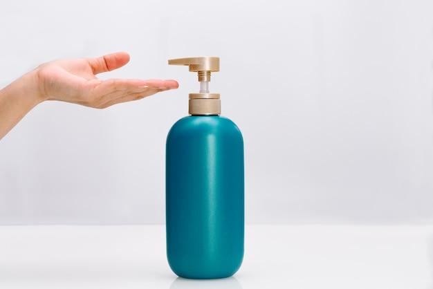 女性の手が白い背景の上の髪シャンプーコンディショナーボトルを適用します。 Premium写真
