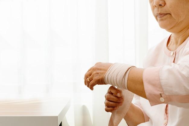 Старушка страдает от боли в руке Premium Фотографии
