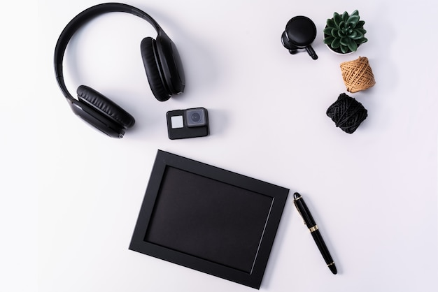 モックアップ、フォトフレーム、アクションカメラ、ヘッドフォン、ペン、そしてサボテン。 Premium写真