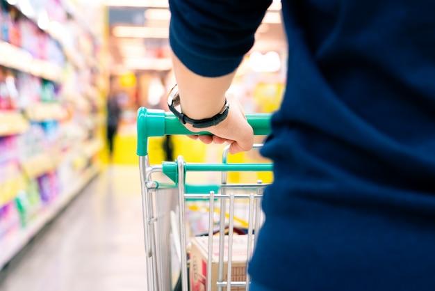 スーパーマーケットデパートのぼやけ動きとトロリーを持つ女性の買い物客 Premium写真