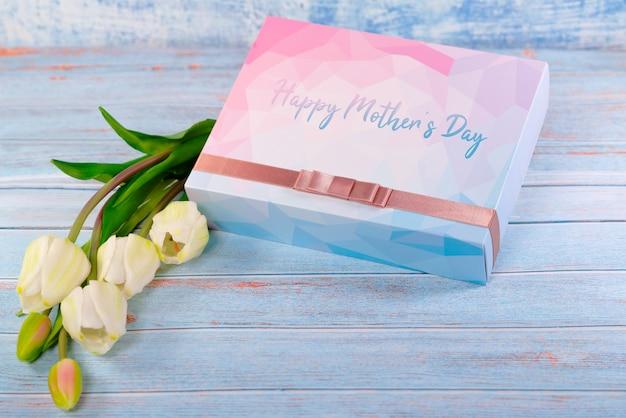 Счастливая концепция дня матери с подарочной коробкой и цветком на деревянном столе Premium Фотографии