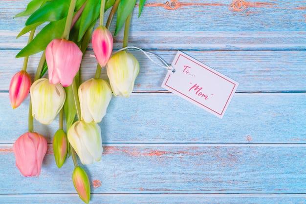 Счастливая концепция дня матери с биркой цветка и бумаги на деревянном столе Premium Фотографии