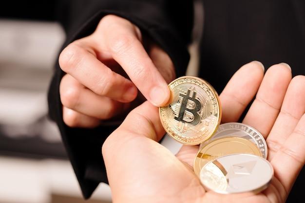 Женщины держат в руках монету криптовалюты. Premium Фотографии