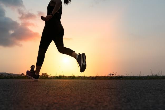 Спортивная женщина работает на дороге. фитнес женщина тренировки на закате Premium Фотографии
