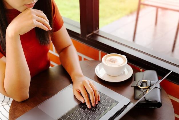 ノートパソコンのキーボードで入力する女性の手。コーヒーを飲みながらオフィスで働く女性 Premium写真
