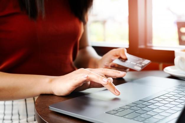 女性手クレジットカードを保持しているとラップトップを使用しています。オンラインショッピング Premium写真