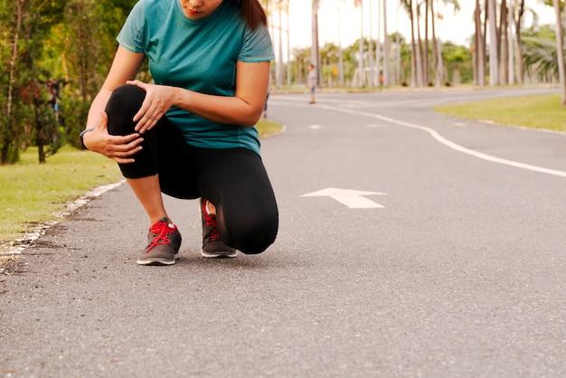 フィットネス女性ランナーが膝の痛みを感じる Premium写真