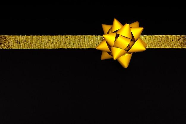 黒の背景、ブラックフライデーセールコンセプトに黄金の弓 Premium写真