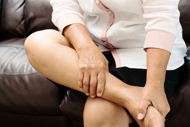 足のけいれん、自宅、健康問題の概念で足のけいれんの痛みに苦しんでいる年配の女性 Premium写真